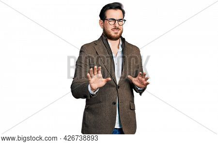 Young hispanic man wearing business jacket and glasses disgusted expression, displeased and fearful doing disgust face because aversion reaction. with hands raised