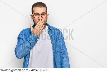 Young caucasian man wearing casual clothes bored yawning tired covering mouth with hand. restless and sleepiness.