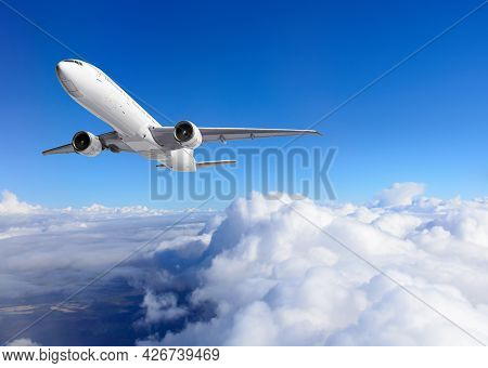 A White Passenger Plane Is Gaining Altitude Taking Off Over The City Through The Clouds Against The
