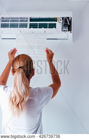 Repair Service Of The Air Conditioner. The Woman Removes The Air Conditioner Filter. Back View. Filt