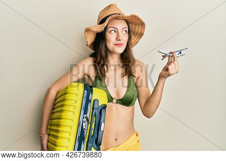 Young brunette woman wearing bikini holding suitcase going on a trip smiling looking to the side and staring away thinking.