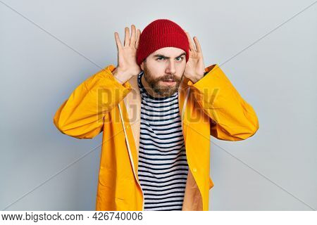 Caucasian man with beard wearing yellow raincoat trying to hear both hands on ear gesture, curious for gossip. hearing problem, deaf