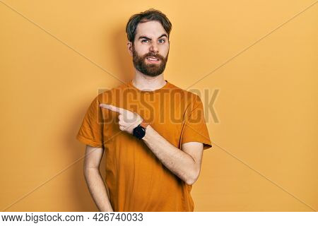 Caucasian man with beard wearing casual yellow t shirt pointing aside worried and nervous with forefinger, concerned and surprised expression