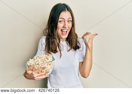 Young brunette woman eating popcorn pointing thumb up to the side smiling happy with open mouth