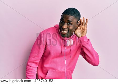 Young african american man wearing gym clothes and using headphones smiling with hand over ear listening an hearing to rumor or gossip. deafness concept.