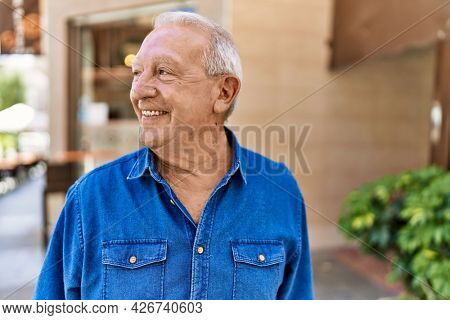 Senior man with grey hair standing happy outdoors on a sunny day. Smiling happy at 70s for retirement.
