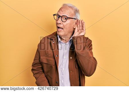 Senior man with grey hair wearing casual jacket and glasses smiling with hand over ear listening an hearing to rumor or gossip. deafness concept.
