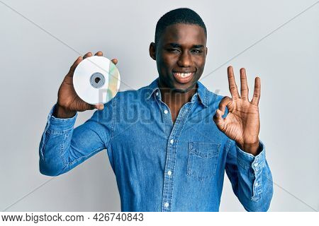 Young african american man holding compact disc doing ok sign with fingers, smiling friendly gesturing excellent symbol