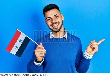 Young hispanic man with beard holding syria flag smiling happy pointing with hand and finger to the side