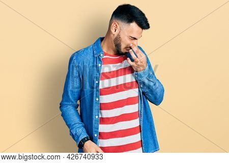 Young hispanic man with beard wearing casual denim jacket smelling something stinky and disgusting, intolerable smell, holding breath with fingers on nose. bad smell