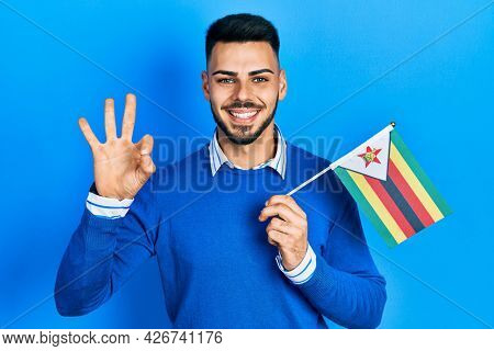 Young hispanic man with beard holding zimbabwe flag doing ok sign with fingers, smiling friendly gesturing excellent symbol