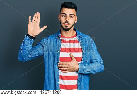 Young hispanic man with beard wearing casual denim jacket swearing with hand on chest and open palm, making a loyalty promise oath