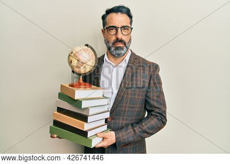 Middle age man with beard and grey hair teacher holding vintage world ball relaxed with serious expression on face. simple and natural looking at the camera.