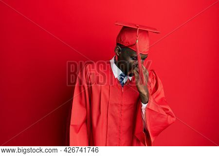 Young african american man wearing graduation cap and ceremony robe smelling something stinky and disgusting, intolerable smell, holding breath with fingers on nose. bad smell