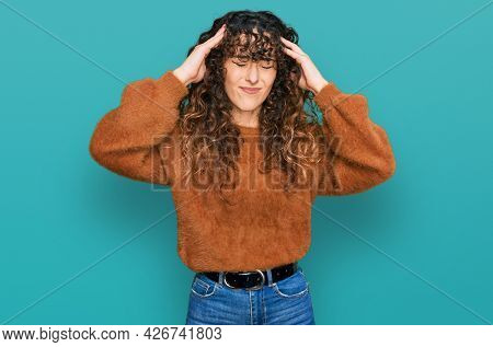 Young hispanic girl wearing casual clothes suffering from headache desperate and stressed because pain and migraine. hands on head.