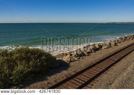 Railroad Tracks Run Parallel To The West Coast Of Southern California On A Cloudless Day. The Tracks