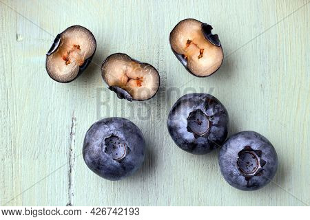 Several Blueberries In A Cut On A Wooden Blue Background