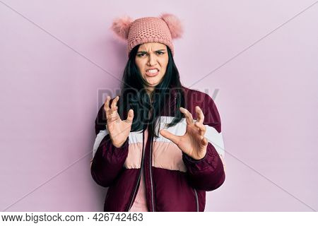 Young hispanic woman wearing wool winter sweater and cap disgusted expression, displeased and fearful doing disgust face because aversion reaction. with hands raised
