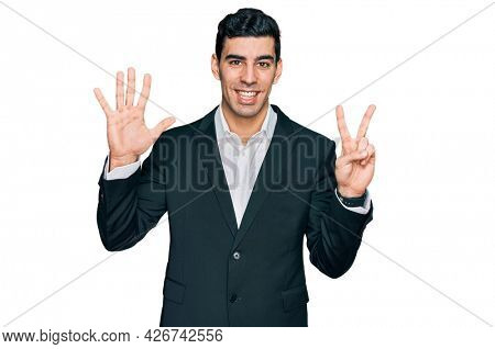 Handsome hispanic man wearing business clothes showing and pointing up with fingers number seven while smiling confident and happy.