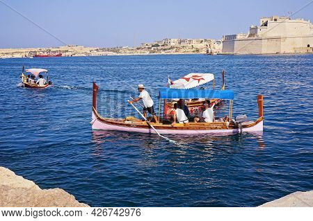 Traditional Water Taxi In Malta From Three Cities And Valletta Harbour. Tourists Sitting In Traditio