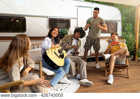 Group Of Diverse Young Friends Having Outdoor Party Near Rv, Playing Guitar, Singing, Drinking Beer,