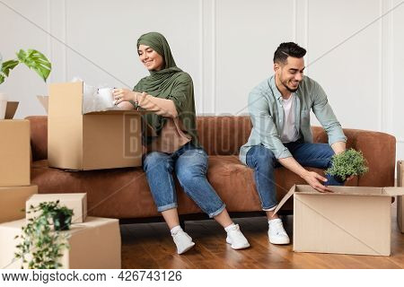 Happy Man And Woman In Hijab Packing Or Unpacking Boxes