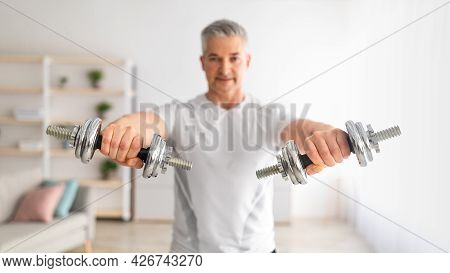 Sporty Mature Man Lifting Dumbells Up Over Living Room Interior, Working On Arms Strength, Selective