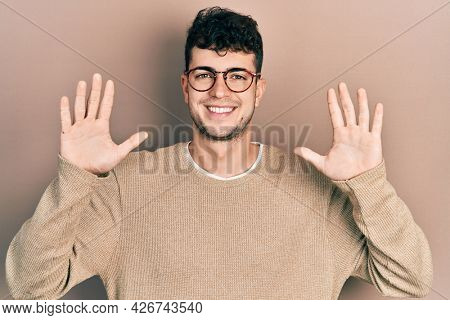 Young hispanic man wearing casual clothes and glasses showing and pointing up with fingers number ten while smiling confident and happy.