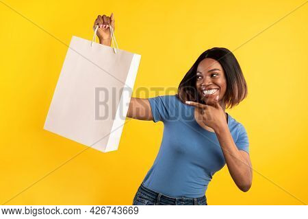 Black Woman Posing Pointing Finger At Shopper Bag, Yellow Background