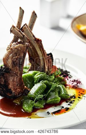 Grilled Rack Of Lamb On A White Plate With Stewed Bean Pods. Restaurant Serving Rack Of Lamb From Th