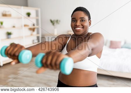 Domestic Weightloss Training. Positive Curvy Black Woman Doing Exercises With Dumbbells, Strengtheni