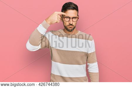 Handsome man with beard wearing casual clothes and glasses pointing unhappy to pimple on forehead, ugly infection of blackhead. acne and skin problem