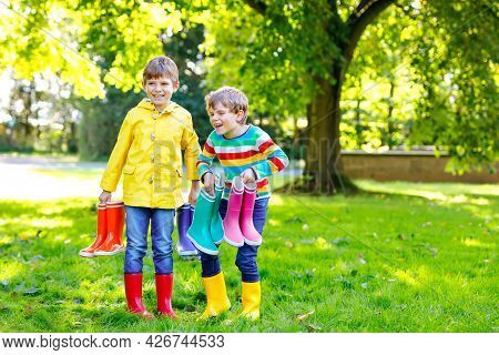 Two Little Kids Boys, Cute Siblings With Lots Of Colorful Rain Boots. Children In Different Rubber B