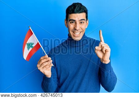 Handsome hispanic man holding lebanon flag smiling with an idea or question pointing finger with happy face, number one