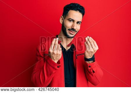 Young hispanic man wearing red leather jacket doing money gesture with hands, asking for salary payment, millionaire business