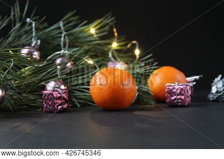 New Year's Christmas Still Life Branch Of Pine Tree Next To The Tangerine Cones Silver Burns Garland