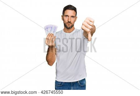 Handsome man with beard holding 20 swedish krona banknotes with angry face, negative sign showing dislike with thumbs down, rejection concept