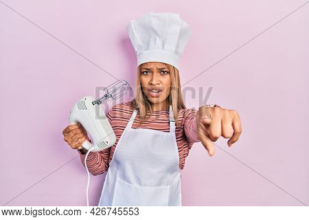 Beautiful hispanic woman holding pastry blender electric mixer pointing displeased and frustrated to the camera, angry and furious with you