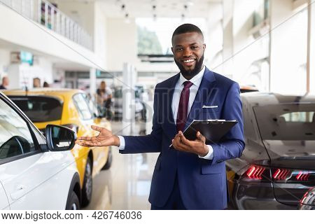 Portrait Of Handsome African American Salesman At Workplace In Car Showroom