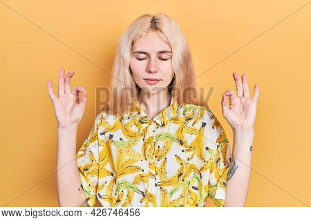 Beautiful caucasian woman with blond hair wearing colorful shirt relax and smiling with eyes closed doing meditation gesture with fingers. yoga concept.
