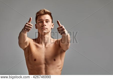 A Swimmer, A Young Athlete In Excellent Physical Shape, Shows With His Hand Urging To Start Training