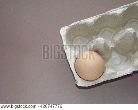 Beige Boiled Eggs In A Pot Of Water With An Egg Box On A Gray Background. High Quality Photo
