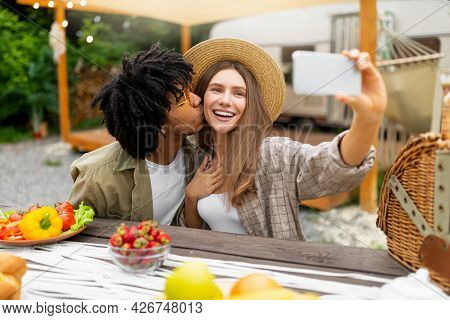 Affectionate Black Guy Kissing His Girlfriend While Making Selfie On Camping Trip, Having Lunch Near