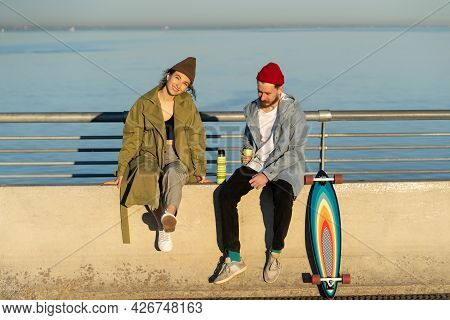 Trendy Young Couple Enjoy Autumn Sunset Sun Sitting With Hot Tea Thermos And Longboard On Concrete B