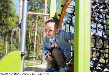 Caucasian Little Boy Climbs The Slide On His Own To Slide Down In The Playground Outdoors On A Sunny