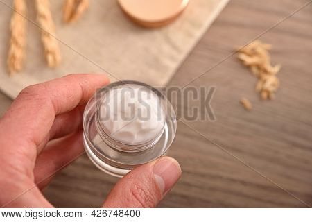 Hand With Glass Jar With Oat Extract Moisturizer With Wooden Table Background With Oat Spikes Top Vi