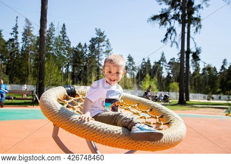 Caucasian Little Boy Riding A Swing In The Playground Outdoors On A Sunny Day.