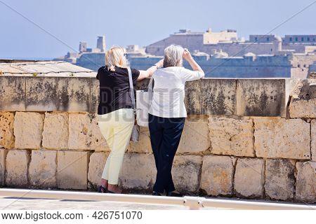Rearview Of Two Elderly Women Admire Views Of Valletta Skyline From Manoel Island Side In Gzira: Man