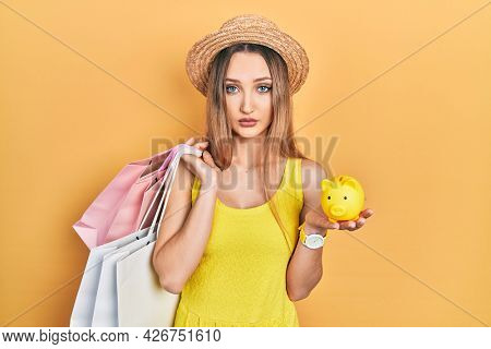 Young blonde girl holding shopping bags and piggy bank relaxed with serious expression on face. simple and natural looking at the camera.