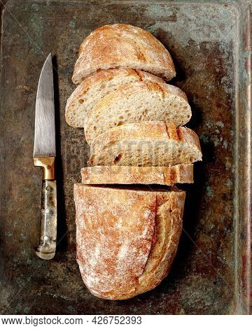 Sliced Bread Ciabatta On Metallic Tray. Top View Of Homemade Ciabatta With Vintage Knife. Flat Lay.